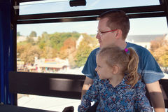 Beautiful man with his pretty happy daughter sitting in ferris w Royalty Free Stock Photography