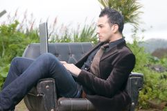 Beautiful man with laptop sitting in an armchair Royalty Free Stock Image