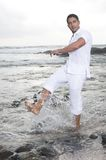 Beautiful man near the sea playing with water. Man near the sea playing with water Royalty Free Stock Photo