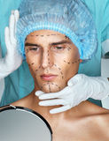 Beautiful Man with perforation lines on his face before plastic surgery operation. Stock Image