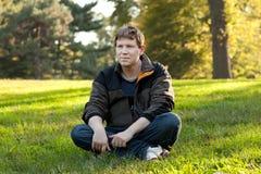 Beautiful man sitting in autumn park Stock Photo