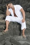 Beautiful man sitting on the rocks Stock Images