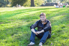 Beautiful man sitting in spring park Royalty Free Stock Photography