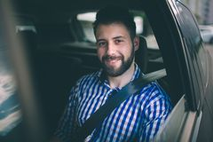 Beautiful man smiling while sitting on back seat in the car royalty free stock photos