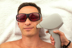 Beautiful man in spa salon having spa therapy with hands of masseur Royalty Free Stock Photography