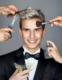 Beautiful man surrounded by the multifunctional service & x28;stylist and hairdresser& x29;. Royalty Free Stock Image