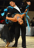 Beautiful man and woman in blue dress perform smiling during dancesport competition Stock Photo