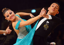 Beautiful man and woman in blue dress perform smiling during dancesport competition Stock Image