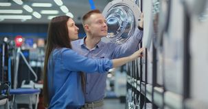 Beautiful man and woman choose modern smart washing machine in consumer electronics store for their new modern home. Beautiful man and woman choose modern smart stock video