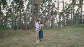 Beautiful man and woman embracing standing in a clearing in the middle of a pine forest. In a romantic couples only love story begins stock footage