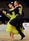 Beautiful man and woman perform smiling during dancesport competition Royalty Free Stock Image