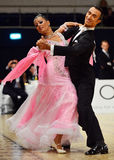 Beautiful man and woman in pink dress perform smiling during dancesport competition Stock Images
