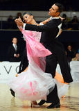 Beautiful man and woman in pink dress perform smiling during dancesport competition Royalty Free Stock Image