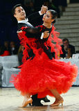 Beautiful man and woman in red dress perform smiling during dancesport competition Stock Photos