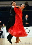 Beautiful man and woman in red dress perform smiling during dancesport competition Stock Photo
