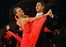 Beautiful man and woman in red dress perform smiling during dancesport competition Royalty Free Stock Image