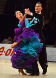 Beautiful man and woman in violet dress perform smiling during dancesport competition Stock Image