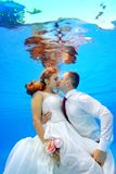 Beautiful man and woman in wedding dresses hugging and kissing underwater in the swimming pool on a background of sun rays. Beautiful men and women in wedding Stock Photo