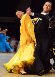Beautiful man and woman in yellow dress perform smiling during dancesport competition Royalty Free Stock Photo