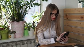 A beautiful manager rewrites with a friend on a smart phone during a lunch break. A beautiful manager with long hair corresponds with a friend on a smart phone stock video