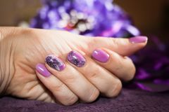 Beautiful manicure with a pattern of lilac stock photography