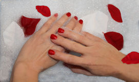 Beautiful manicured hands in babbles Stock Photography