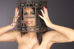 Beautiful Manicured Woman Holding Head Inside Metal Bird Cage Stock Image