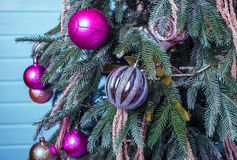 Beautiful Marble-balls hanging on the Christmas tree, shining colorful garland. On the branches covered with snow. Stock Photo
