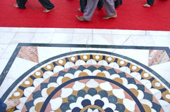 Beautiful marble floor and barefooted sikh prayers foots on red carpet Stock Photos
