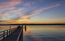 Beautiful marine sunset over a pier. Or jetty tinting the clouds a delicate pink and gold above a tranquil ocean Stock Image