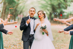 Beautiful married couple attaching to face paper mustache, glasses, bow Stock Image