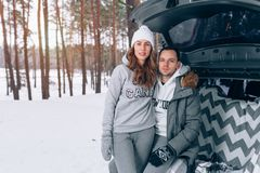 Beautiful family couple in a snowy winter forest sitting in the. A beautiful married couple in a snowy winter forest sits in the trunk of their car. Dressed in Royalty Free Stock Photos