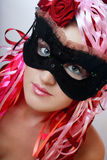 Beautiful mask. Portrait of girl with beautiful eyes in fancy lacy masque and wig of colorful silk ribbons on her head Stock Image