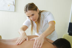 Beautiful masseuse applying massage to male client Royalty Free Stock Photo