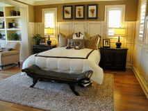 Beautiful Master Bed Room. With wood floors wood shudders and a sitting room Royalty Free Stock Photography