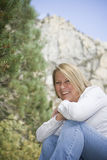 Beautiful Mature Adult Outdoors. Healthy mature woman in an outdoor setting with an evergreen tree and rock/mountain behind her Stock Images