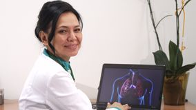 Mature female doctor examining lungs scan on her laptop at the clinic