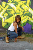 Beautiful Mature Black Woman with Graffiti (12). A lovely mature black woman, wearing denim bib overalls with work boots and a white tank top, squats in front of Vector Illustration