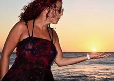 Beautiful mature brunette on beach blowing on sun stock image