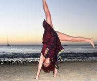Beautiful mature brunette doing cartwheel on the beach royalty free stock image
