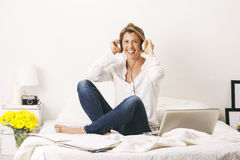 Beautiful mature business woman listening music with headphones. Break time. Royalty Free Stock Photo