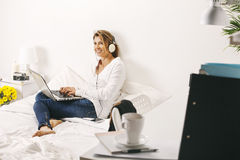 Beautiful mature business woman listening music and working with laptop. Royalty Free Stock Photo