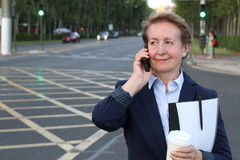 Beautiful mature businesswoman using cell phone on busy city street Stock Images