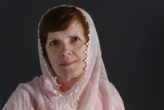 Beautiful mature Caucasian woman wearing cream-colored shawl against dark background Stock Photos