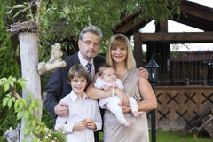 Beautiful mature couple in formal dress and suit with two kids in a garden Royalty Free Stock Photos