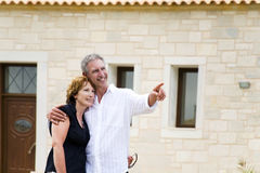 Beautiful mature couple in front of their house. Beautiful mature couple standing in front of their new house Stock Photography