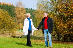 Romantic couple holding hands walking stock image
