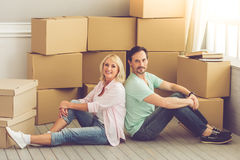 Beautiful mature couple moving. Beautiful mature couple in casual clothes is looking at camera and smiling while sitting back to back on the floor among boxes Royalty Free Stock Image