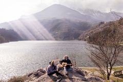 Beautiful mature couple playing a guitar sitting on the lake royalty free stock images