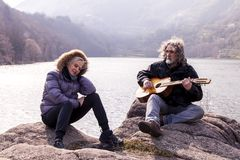 Beautiful mature couple playing a guitar sitting on the lake stock photos
